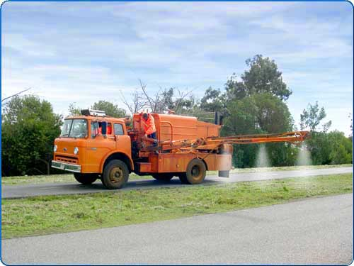 The arm of this truck is extending over the grass. Spraying herbicide onto the weeds kills the weed from the leaves to the root. The preemergent is applied to prevent the growth of weeds.